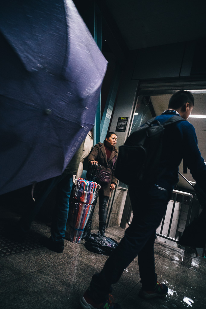 """Selling Umbrellas by Metro Exit when Unexpected Rain Came"" by Gino Zhang, on Flickr, on 500px"